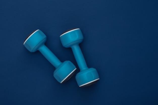 古典的な青い背景のダンベル。健康的なライフスタイル、フィットネストレーニング。カラー2020。上面図