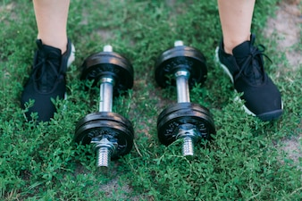 Dumbbells on green grass background and foots in black sneakers
