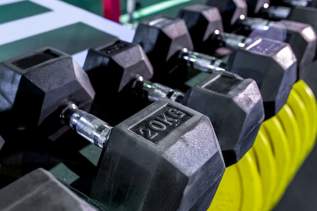 Dumbbells, pancakes and weights lying on the shelves. gym. equipment for gym