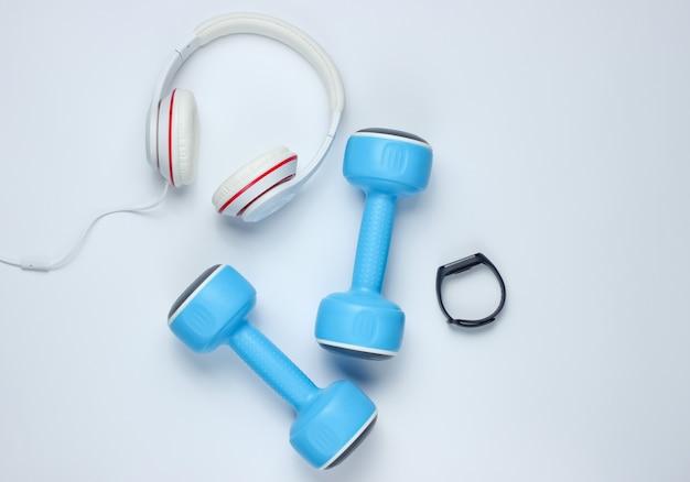 Гантели, умный браслет, наушники на белом фоне. минималистичная спортивная концепция. вид сверху.