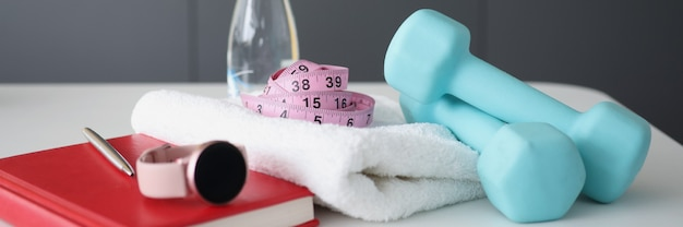 Dumbbells smart watches and diary with water are on table