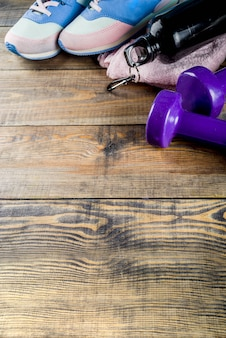 Dumbbells, sneakers, a towel and a bottle of water on wooden background
