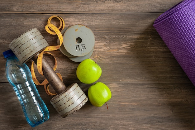 Dumbbells, sports mat, tablet on a wooden background. the concept of fitness and health. top view with a space for text.
