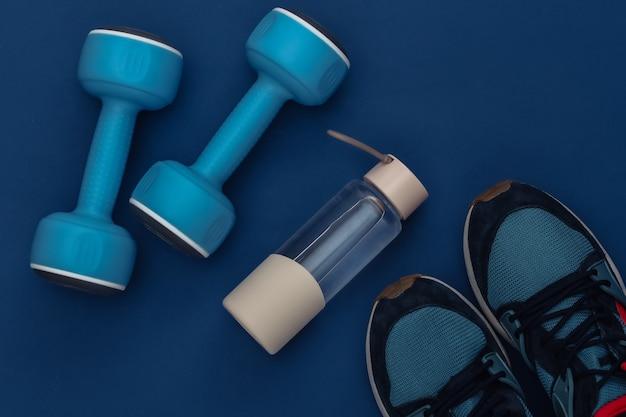 クラシックな青い背景にダンベル、ウォーターボトル、スニーカー。健康的なライフスタイル、フィットネストレーニング。カラー2020。上面図