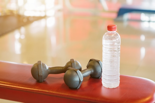 Dumbbells and water bottle on a bench a empty red in defocused sport gym interior