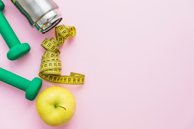 Dumbbells; water bottle; measuring tape and apple on pink background