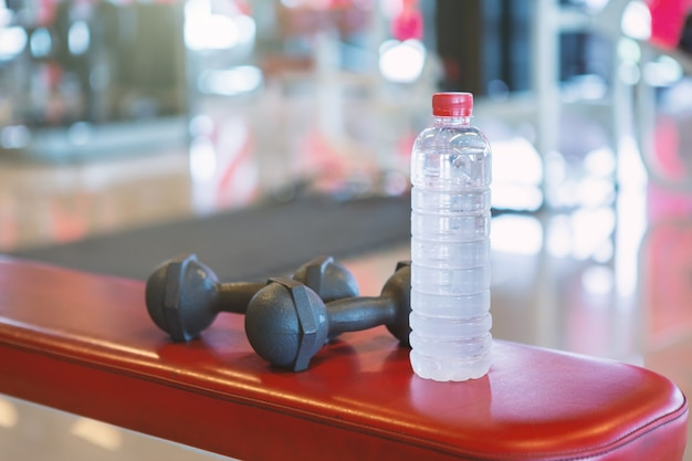 Dumbbells and water on a empty black rubber floor floor in defocused sport gym interior