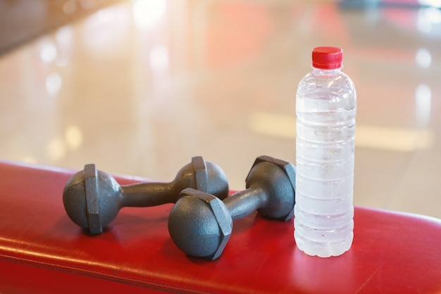 Dumbbells and water on a empty black rubber floor floor in defocused sport gym interior an