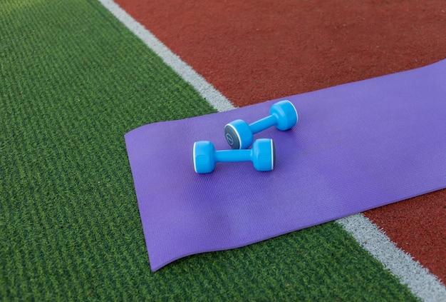 スタジアムにマットが付いたダンベル。屋外トレーニング