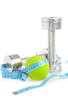 Dumbbells with an apple on a white wall. a healthy way of life