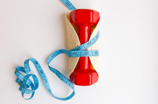 白地にピタブルーの巻尺で包まれたダンベル。減量と適切なフィットのライフスタイル、ダイエット、スポーツのコンセプト
