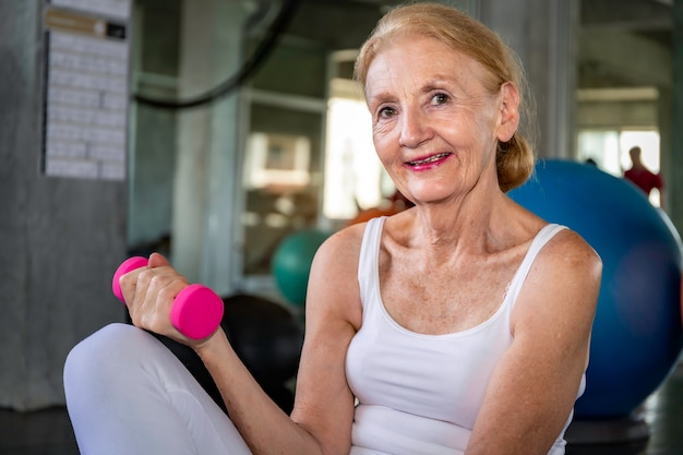Рука тренировки старшей женщины кавказская с dumbell на спортзале фитнеса.