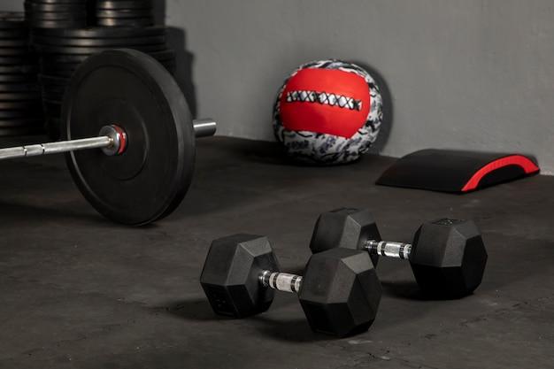 Dumbells para hacer ejercicio en un gimnasio con pesas y una pelota medicine