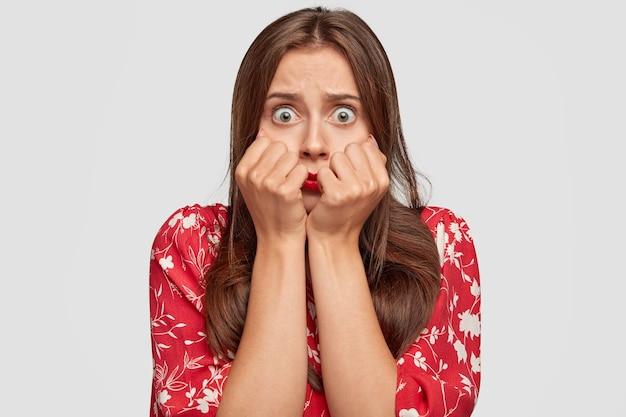 Donna sbalordita con rossetto rosso in posa contro il muro bianco