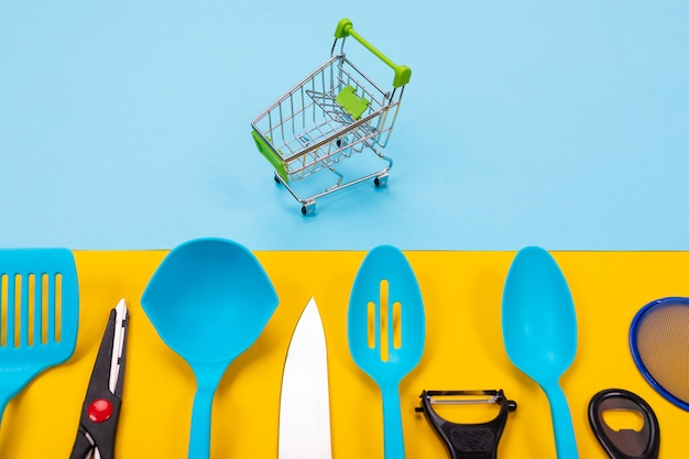 Dummy shopping cart and kitchen utensils isolated on yellow blue