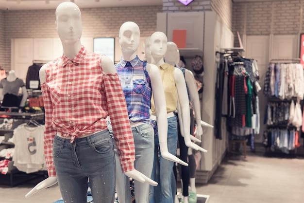 Манекен показывает одежду внутри дорогого магазина.