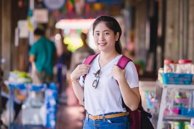 Dumonoe saduak水上マーケット、タイで歩く若いアジアの女の子