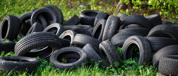 Dump of old used tires on fresh green grass in the forest.