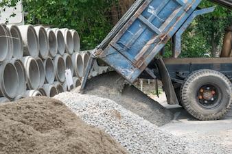 Dump truck unloading sand at construction site