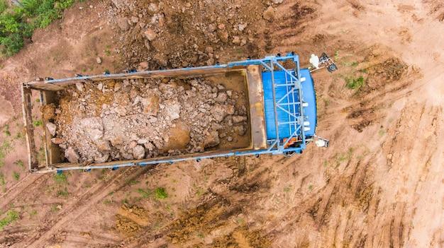 Dump truck unloads soil on the construction site. aerial view