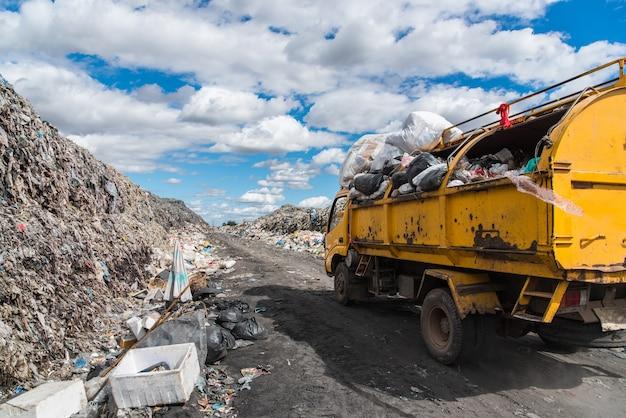 Dump trucks unloading garbage over vast landfill