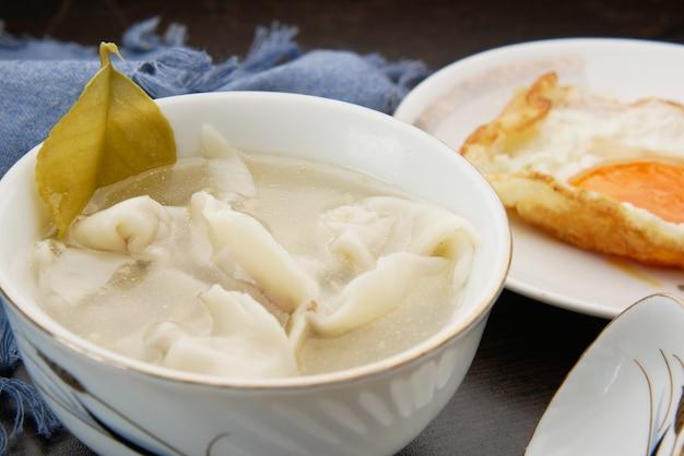 Суп с клецками в миске на столе,