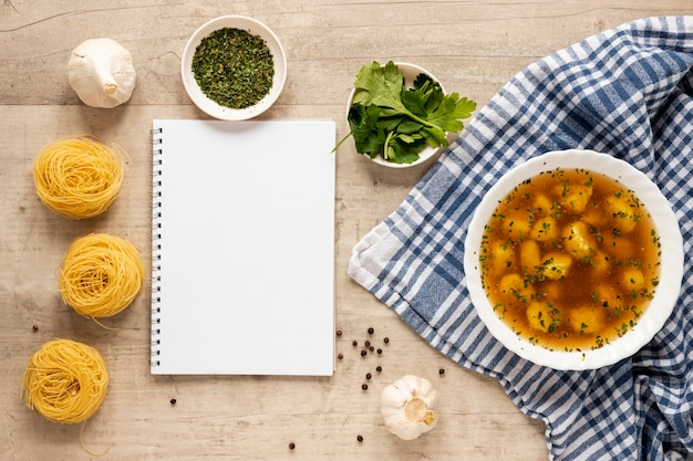 Dumpling soup with pasta and notepad