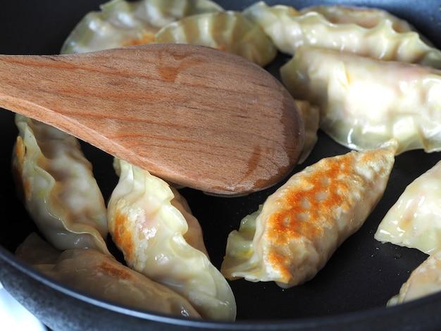 만두는 팬에 튀겨집니다. 다양한 충전재가 있는 아시아 요리. 튀김 교자
