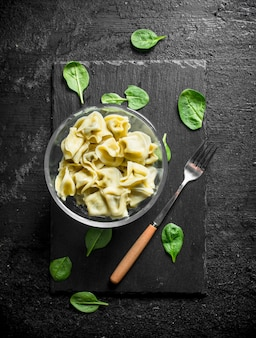 Dumplings in a bowl with spinach leaves on black rustic table