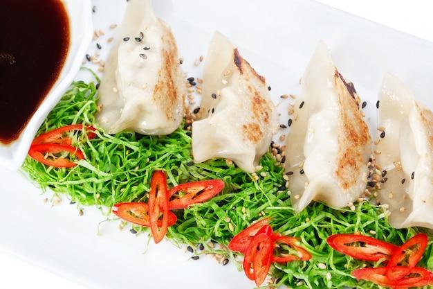 초밥 제품으로 가득한 만두를 닫습니다. 검은 식초와 샐러드.