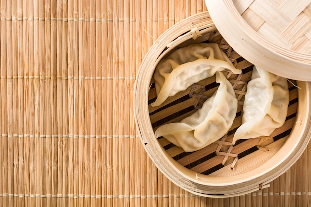 Dumplings or gyoza served in traditional steamer and soy sauce on bamboo mat copy space