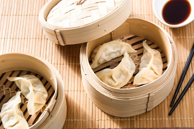 Dumplings or gyoza served in traditional steamer and soy sauce on bamboo mat