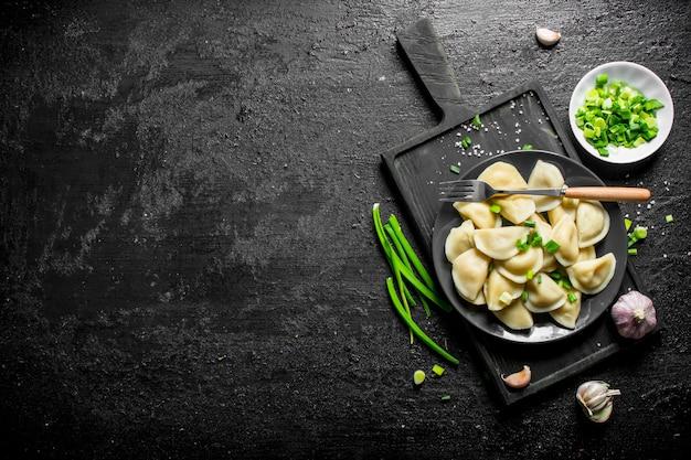 녹색 양파와 마늘 검은 시골 풍 테이블에 접시에만 두.