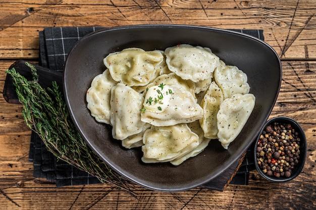 허브와 버터를 곁들인 접시에 감자를 넣은 만두 피에로기