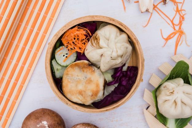 Dumplings and salad in steamer on backdrop