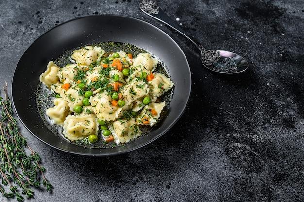 야채와 함께 그릇에 라비올리 파스타와 만두 수프. 검은 배경. 평면도. 공간을 복사합니다.