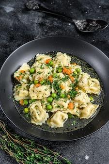 채소와 함께 그릇에 라비올리 파스타와 만두 수프. 검정색 배경. 평면도.