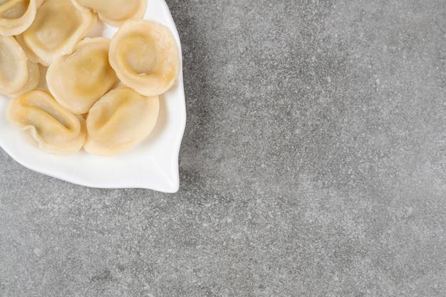 白い皿に肉を詰めた餃子