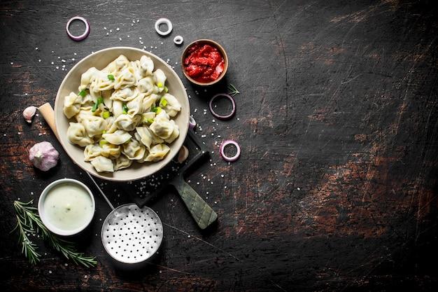 파, 사워 크림, 로즈마리, 토마토 페이스트를 곁들인 만두. 어두운 소박한 배경에