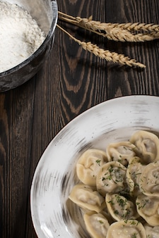 肉入り餃子。白い皿の上のロシアの郷土料理。木の板