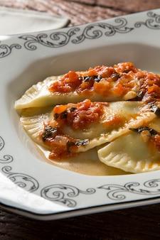 접시에 토마토와 고기 만두-pierogi