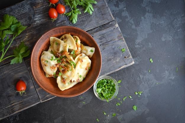 Пельмени с картофельной начинкой. пельмени в глиняной тарелке. вид сверху.