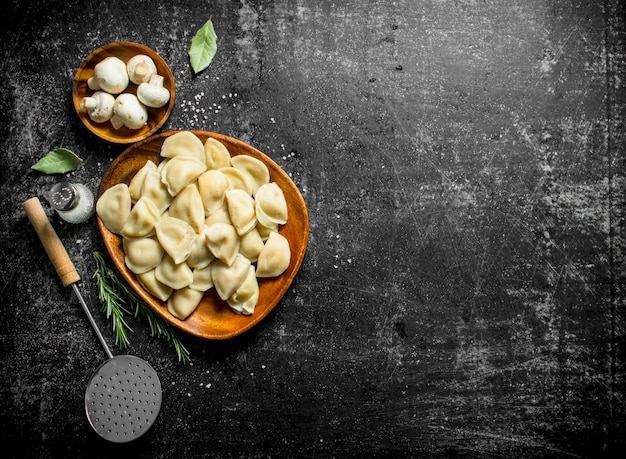 Dumplings with sour cream, bay leaf and mushrooms. on dark rustic background