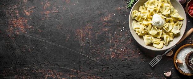 Dumplings with sour cream and spices. on dark rustic background