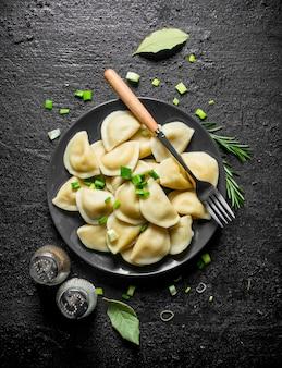 검은 시골 풍 테이블에 향신료, 로즈마리, 파와 만 두.