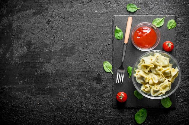 토마토 페이스트와 검은 시골 풍 테이블에 시금치와 만 두.