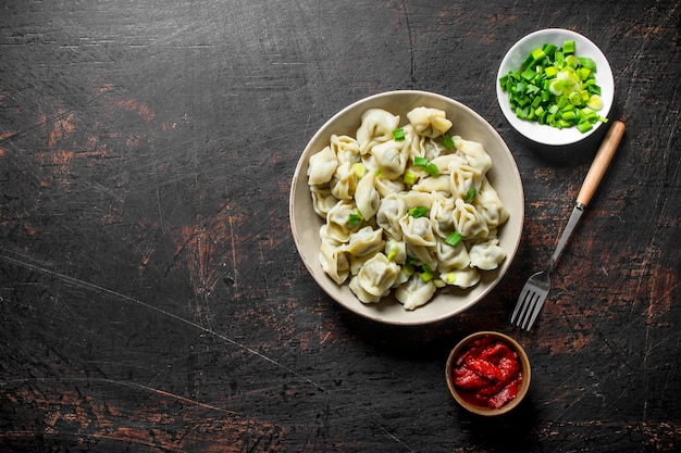 Dumplings with tomato paste and chopped green onions.