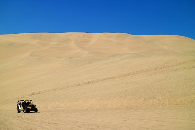 Dune buggy running up onto the sand dunes of huacachina desert in ica region, peru