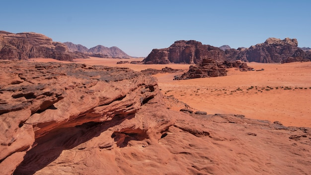 Dunes in red desert with rocks wadi rum in jordan during the day in the hot sun in summer