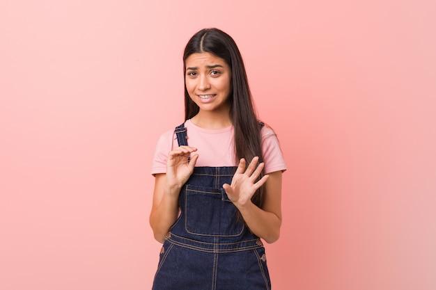 Молодая милая арабская женщина нося джинсы dungaree отвергая кто-то показывая жест отвращения.